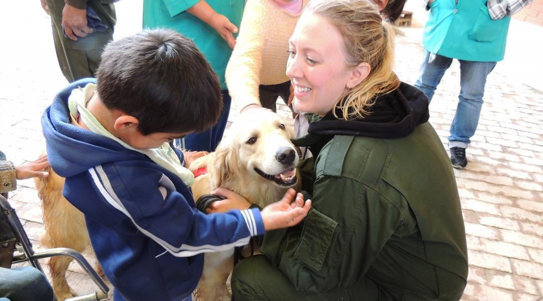 Voluntaria interactuando con un perro en su voluntariado de cuidado animal.An intern bonds with a dog on a Projects Abroad Animal Care internship abroad.